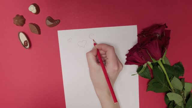 A woman draws hearts on a white sheet of paper with a red pencil. Love letter.