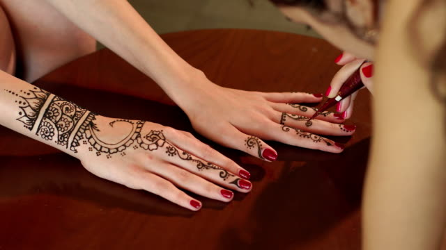 Woman draws mehendi on the hands in a beauty salon video