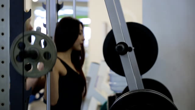 Woman dressed in black costume trains hard in gym video