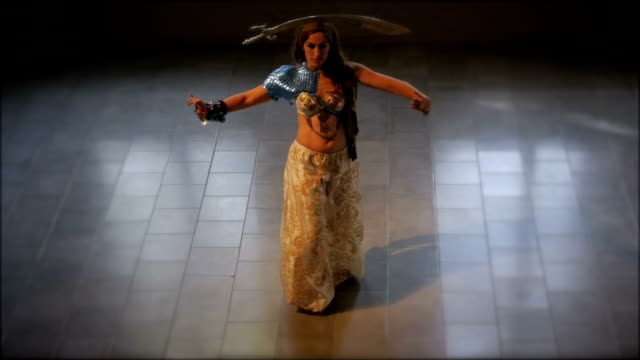 A woman dressed in traditional ethnic clothing dancing with a sword on her head video