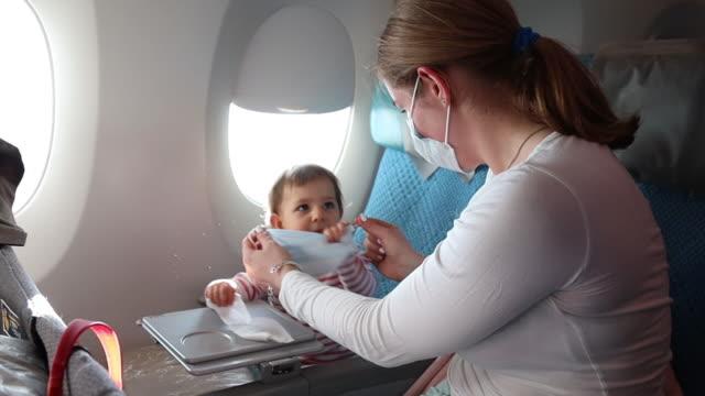 kadın bir uçakta koruyucu bir yüz gazlı bez bandaj elbise. bir çocuğa maske takmaya çalışıyorum. direniyor. korona virüsüne karşı koruma, solunum yolu enfeksiyonları grip. covid 19 mücadele - maske stok videoları ve detay görüntü çekimi