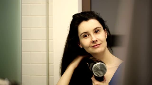 Woman dries hair in the bathroom video