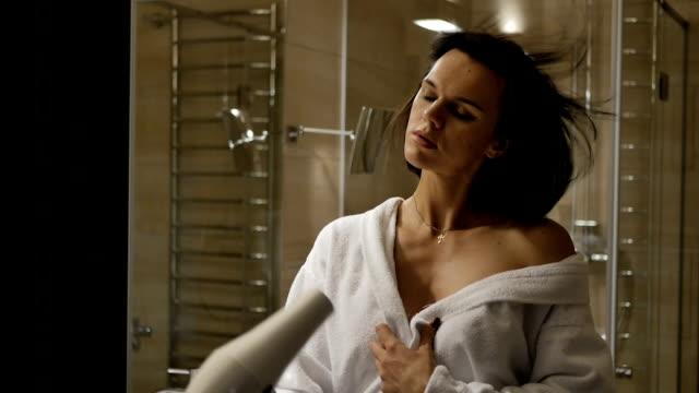 Woman dries hair the hair dryer. video