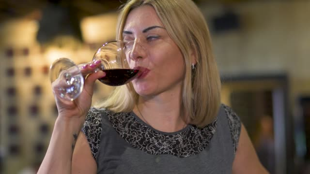 Woman drink red wine at restaurant Woman in gray clothing drinks red wine from wineglass. Lady is resting in cafe. Blurred background. tasting stock videos & royalty-free footage
