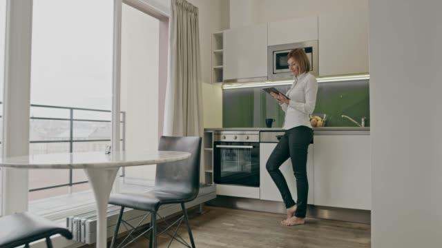 彼女のアパートでタブレットを使用している間、コーヒーを飲みながら ws 女性 - 広角撮影点の映像素材/bロール
