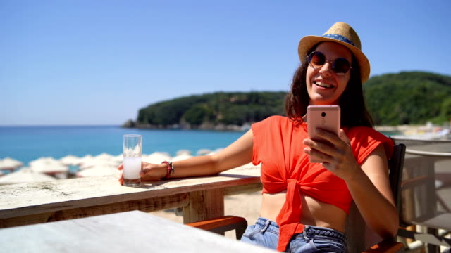 Woman drinking and texting on beach terrace