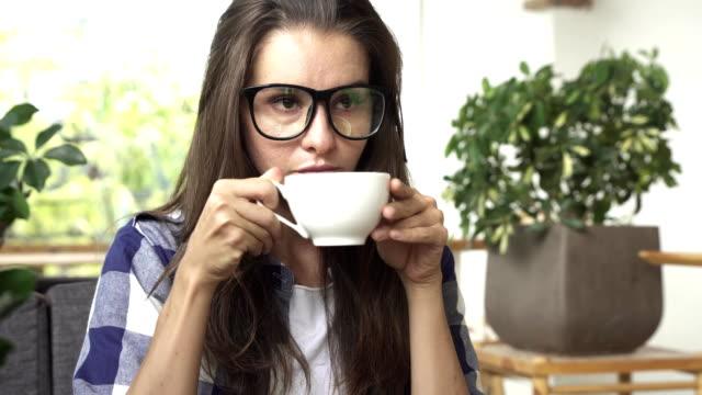 frau, trinken kaffee und lächelt. - grüner tee stock-videos und b-roll-filmmaterial