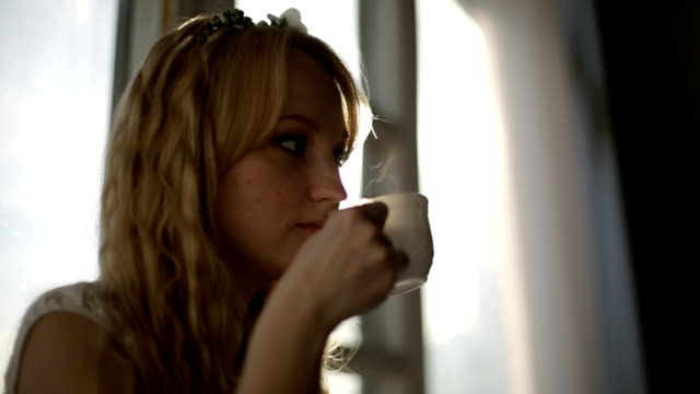 Woman drinking coffee by the window during sunrise video