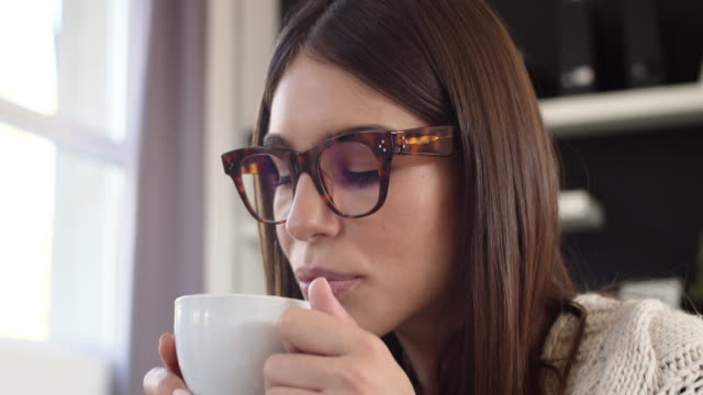 woman drinking coffee in bedroom. - annusare video stock e b–roll