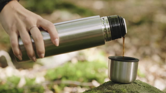 Woman drinking coffee in the forest