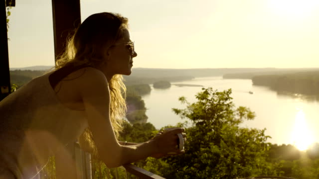 Woman drinking coffee in the sun, outdoor in sunlight light. video
