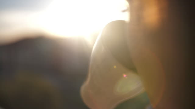 woman drinking coffee on the balcony admiring the sunset, close up video