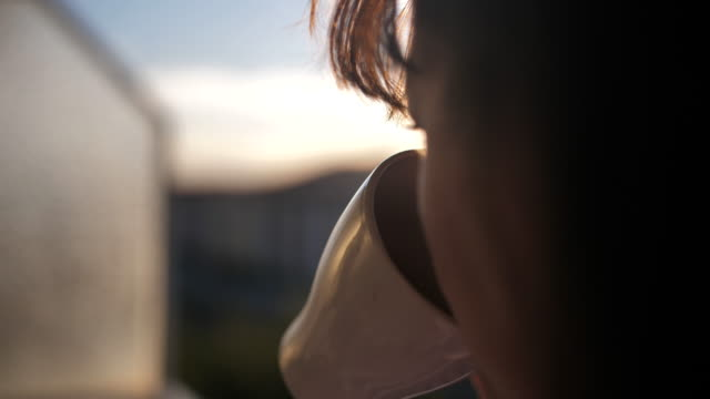 woman drinking coffee on the balcony, admiring the sunset, slow motion video