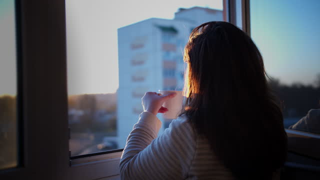 Woman drinking coffee on the balcony at sunset, back view, enjoying the sunset video