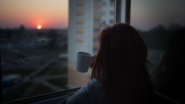 Woman drinking coffee on the balcony at sunset, back view, video