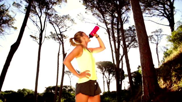 stockvideo's en b-roll-footage met woman drinking cool water after a run in slow motion - handen op de heupen