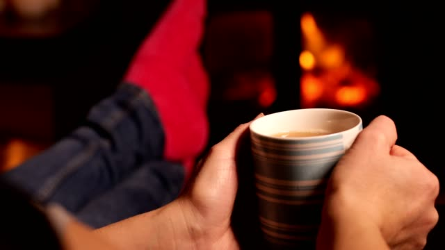 vídeos de stock e filmes b-roll de woman drinking cup of tea warming feet by flames of wood burning stove - hygge