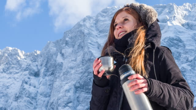 Woman drinking from a thermos in snowy mountains video