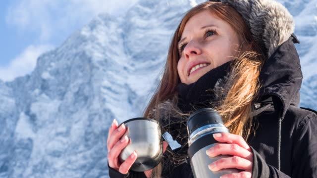 vidéos et rushes de femme buvant à un thermos dans les montagnes enneigées - boisson chaude