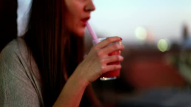 Woman drinking fruit smoothie on terrace video