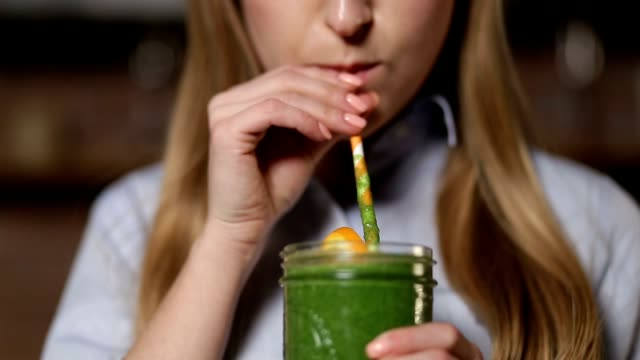 Woman drinking green detox vegetable smoothie video