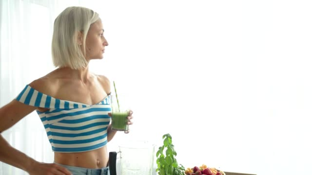 woman drinking green vegetable smoothie at kitchen. healthy eating lifestyle - healthy green juice video stock e b–roll
