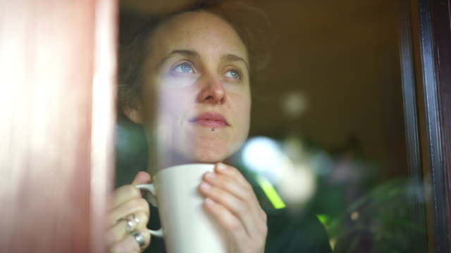 vídeos de stock e filmes b-roll de woman drinking hot beverage looks out of window from inside her apartment - isolado