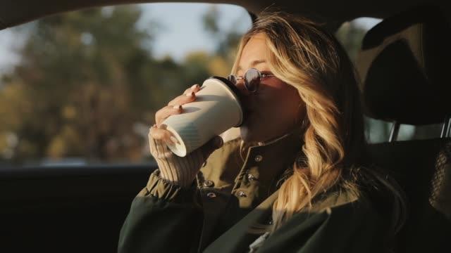 Woman drinking hot tea in a car video