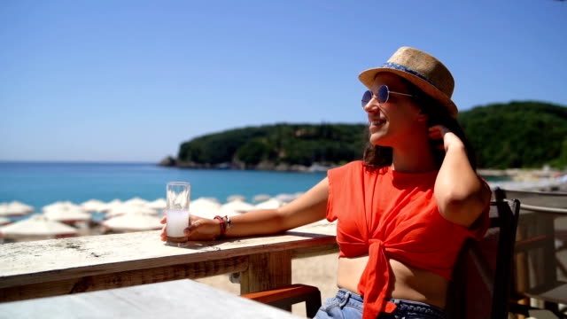 Woman drinking on beach terrace Young cute caucasian woman drinking ouzo on beach terrace at seaside. aperitif stock videos & royalty-free footage