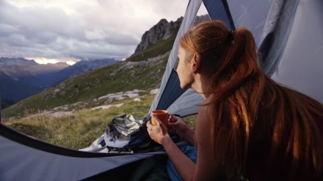 stockvideo's en b-roll-footage met vrouw het drinken van thee in de tent hoog in de bergen en het bewonderen van de weergave - paardenstaart haar naar achteren
