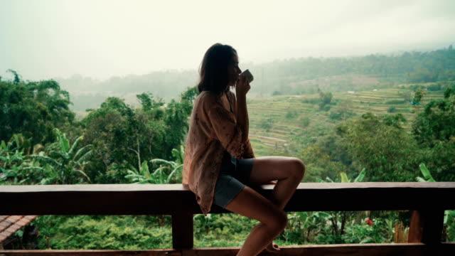 vidéos et rushes de femme buvant du thé sur balcon avec vue sur les rizières - thé boisson chaude