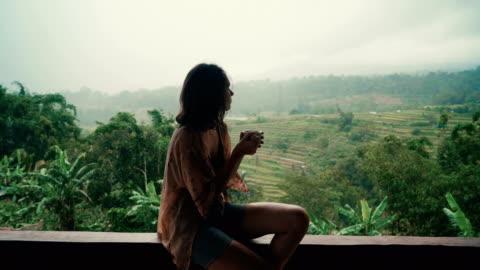 vídeos y material grabado en eventos de stock de mujer bebiendo té en el balcón con vistas a campos de arroz - viajes