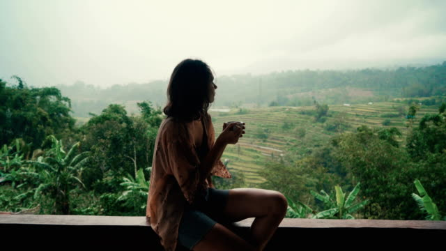 woman drinking tea on balcony with view  on rice fields - bali filmów i materiałów b-roll
