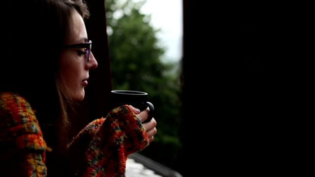 Woman Drinking Tea Or Coffee And Looking Out Window video