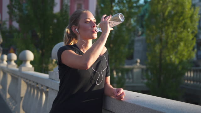 Woman drinking water after exercise video