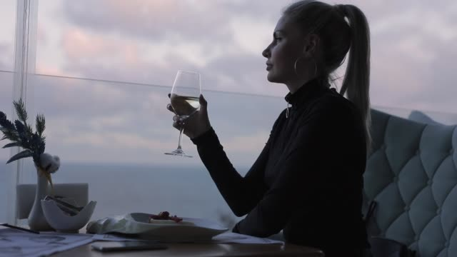 Woman drinking white wine in restaurant with sea view video