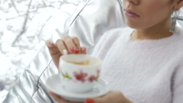 Woman drinks coffee near the window video