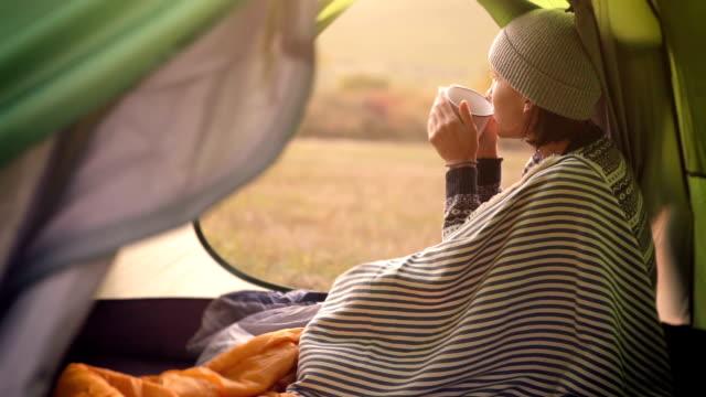vídeos de stock, filmes e b-roll de mulher bebidas quente chá na barraca de acampamento e desfrutar com a noite de outono, no vale da montanha - tea drinks