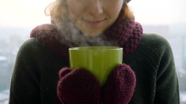 Woman drinks hot tea or coffee from green cup on winter morning video
