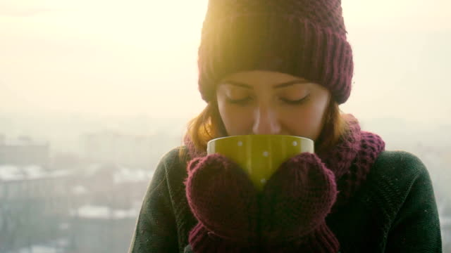 woman drinks hot tea or coffee from yellow cup on winter morning - bevanda calda video stock e b–roll