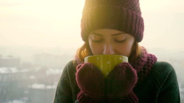 vidéos et rushes de femme boissons chaudes thé ou café de jaune coupe du matin d'hiver - thé boisson chaude