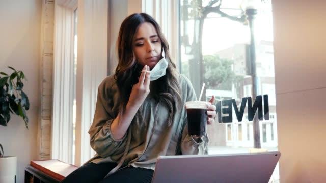 vídeos de stock e filmes b-roll de woman drinks iced coffee in coffee shop while wearing protective face mask - café gelado