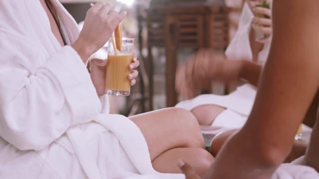 vidéos et rushes de femme boit le jus d'orange au spa - peignoir