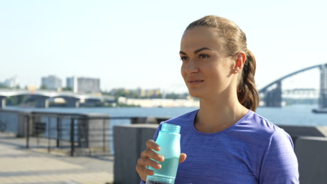 Woman drinks water and shows thumb up against urban background Young attractive woman stands against city view with river and bridges. She drinks water from her bottle. Looking to the camera, she smiles and gives thumb up sleeve stock videos & royalty-free footage