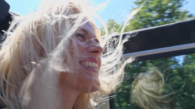 woman driver on road trip in convertible car - spettinato video stock e b–roll