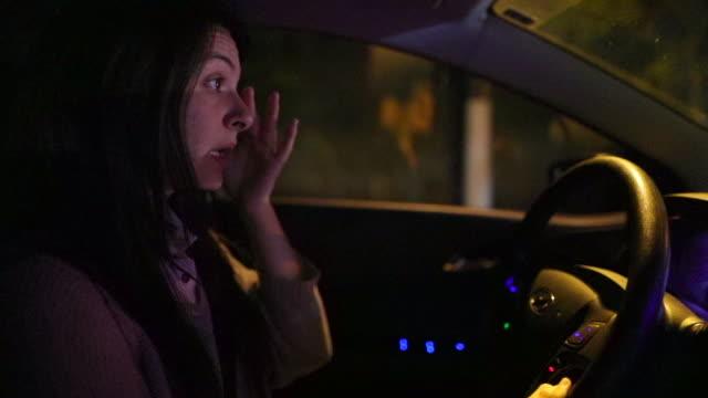 Femme, conduite de nuit, frottant son visage fatigué d'une longue journée de travail. La conductrice fatigué la conduite de nuit faire la navette entre travail - Vidéo