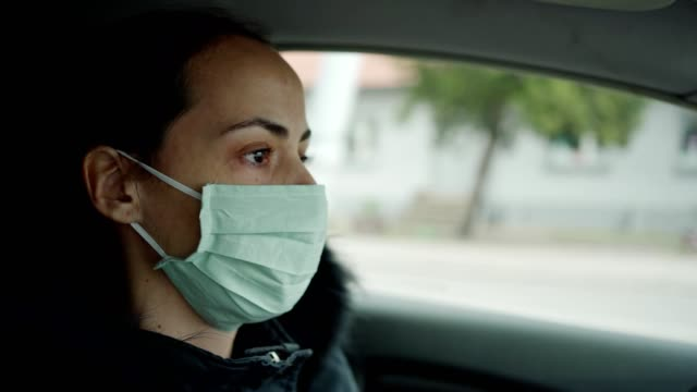 woman driving car with protective mask - autista mestiere video stock e b–roll
