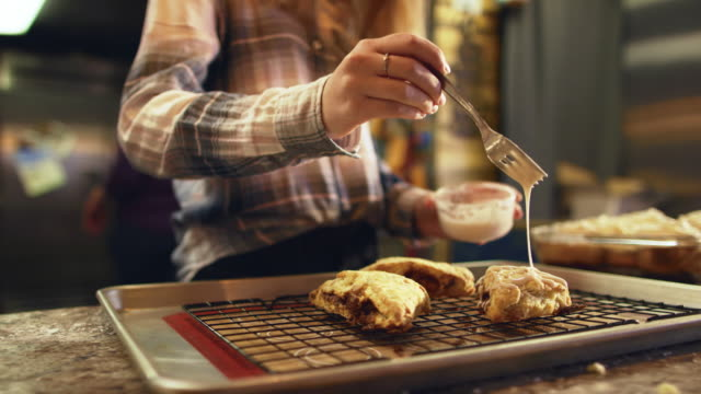 a woman drizzles icing on to homemade scones in a bakery - scone filmów i materiałów b-roll