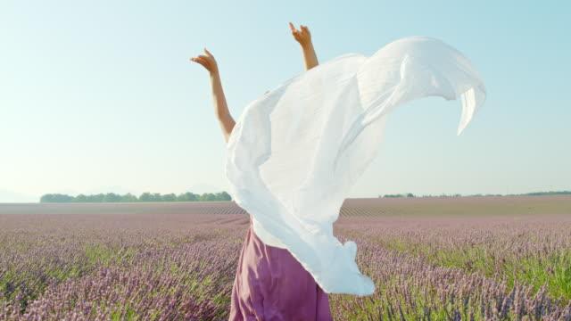 slo mo женщина снижается белый шарф в лавандовом поле - эффект деформации времени - шарф стоковые видео и кадры b-roll