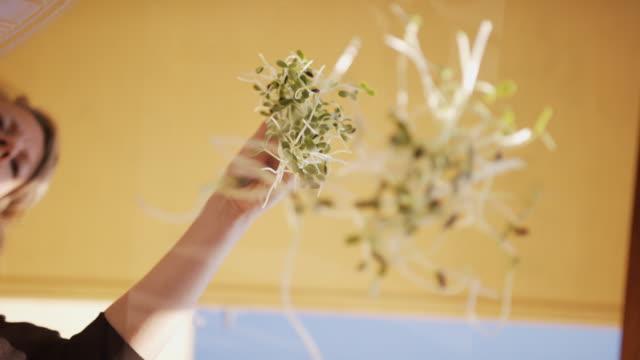 Woman dropping microgreens on camera looking up